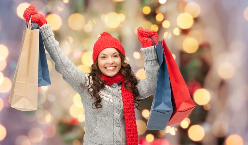 holidays x-mas sale and people concept - happy young asian woman in winter clothes with shopping bags over christmas tree lights background