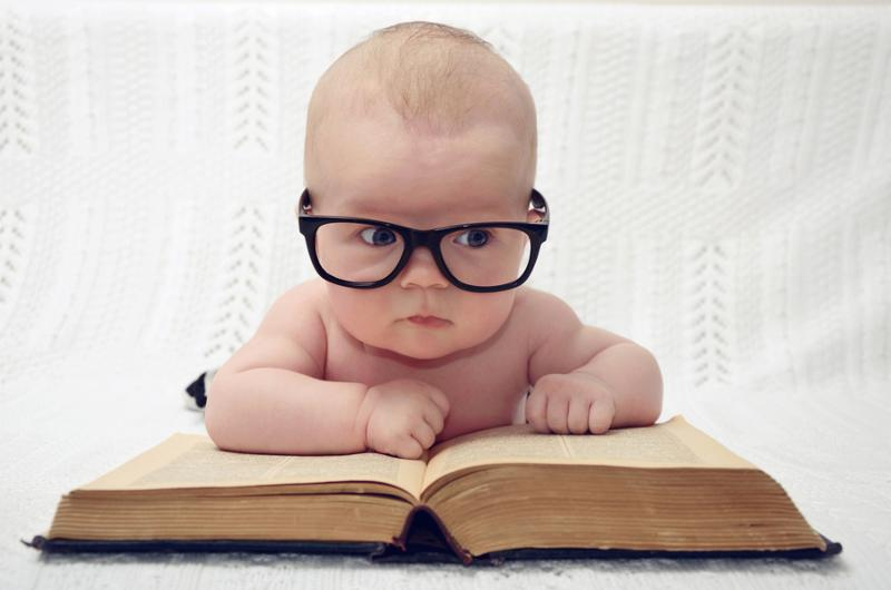 funny portrait of adorable little baby in glasses with old book  thinking expression
