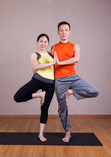Couple perform Double Tree yoga partner pose in studio