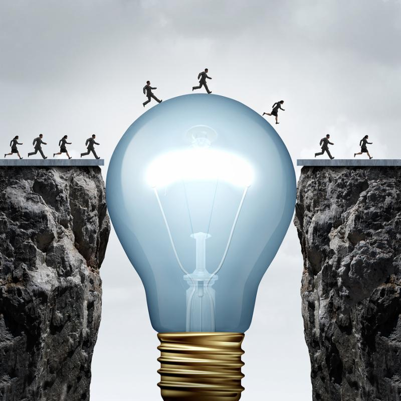 Creativity business idea solution as a group of people on two divided cliffs being connected by a giant light bulb closing the gap and creating a bridge to enable a crossing to success as a cretive thinking metaphor..