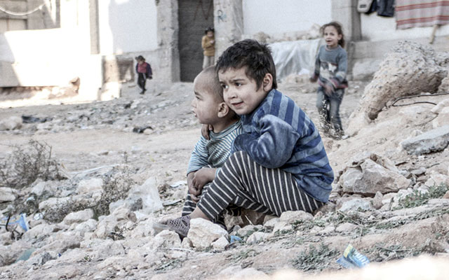 In Aleppo, Syria, four-year-old Esraa and her brother Waleed, three, sit on the ground near a shelter for internally displaced persons. Photo: UNICEF/UN013175/Al-Issa.