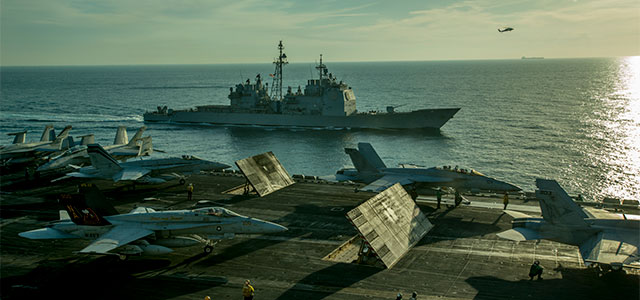 Guided-missile cruiser USS Bunker Hill alongside aircraft carrier USS Carl Vinson during flight operations supporting Operation Inherent Resolve, operations in Iraq and Syria, maritime security operations, and theater security cooperation efforts in the Arabian Gulf. Photo: U.S. Navy.