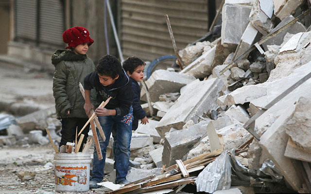 Children collect firewood amid damage and debris at a site hit by airstrikes in the al-Shaar neighborhood of Aleppo, Syria November 17, 2016. Photo: REUTERS/Abdalrhman Ismail.