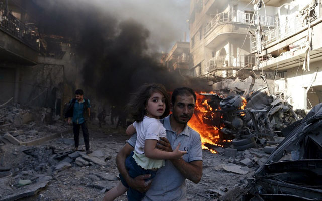 A man carries a girl as they rush away from a site hit by airstrikes from forces loyal to Syria's President Bashar al-Assad in the Douma neighborhood of Damascus, Syria, on August 24, 2015.