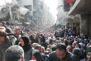 The besieged Palestinian camp of Yarmouk queuing to receive the first humanitarian supplies after six months of siege, in Damascus, Syria, in January 2014. According to the United Nations High Commissioner for Refugees over 3 million people have fled Syria to Turkey, Lebanon, Jordan and Iraq, while 6.5 million people are internally displaced within Syria.