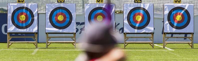 A person is shooting with recurve bow on a target during an archery competition. Focus on the targets.     Note  Soft Focus at 100 , best at smaller sizes