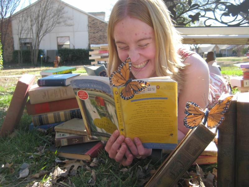 Mel on the grass, surrounded by books, and reading one, except that it's upside down, and charmingly, has a butterfly perched on it :)